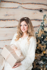 Beautiful girl in white dress sitting near a beautiful tree