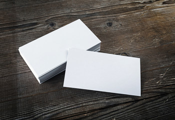 Photo of blank white business cards on a dark wooden background. Mock-up for branding identity. Blank template for design presentations and portfolios.
