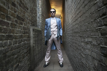 man dressed in a blue colored suit and sunglasses standing to lean at brick wall.