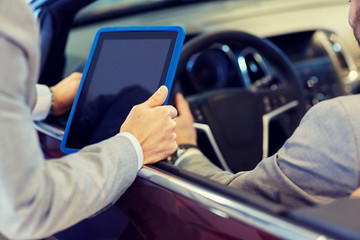 close up of men with tablet pc in car salon