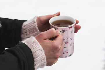 Kobieta piję gorącą herbatę w zaśnieżonej scenerji