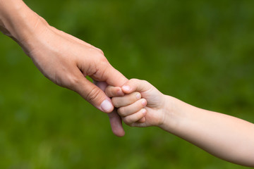 adult holding a hand of child