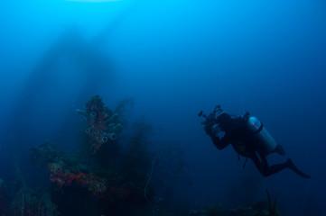 Underwater photographer exploring wreck ship in the deep.
