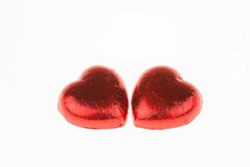 Red Foil wrapped heart shaped chocolates isolate on white backgr