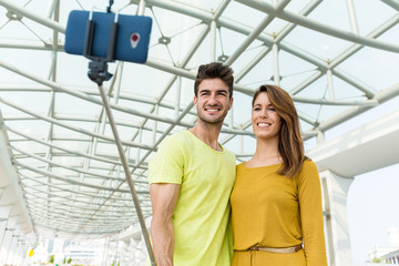 Caucasian young couple use mobile phone for taking photo