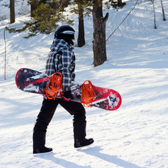 The young snowboarder goes uphill