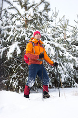 The guy comes in snowshoes through the snow in a winter hike.