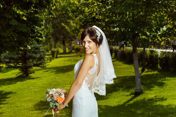 Happy smiling bride with is standing at green summer park