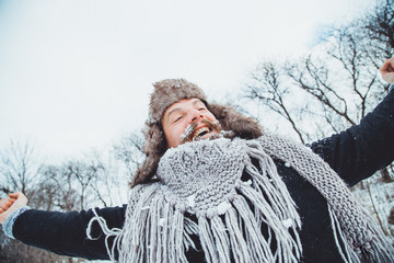 Funny young bearded man in the winter in nature. The man raised his hands up rejoices winter.