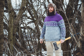 Portrait of a Bearded Man with an ax in his hand.North bearded man with an ax in the woods.