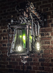 Metal street lamp in the style of steampunk on the brick wall background included