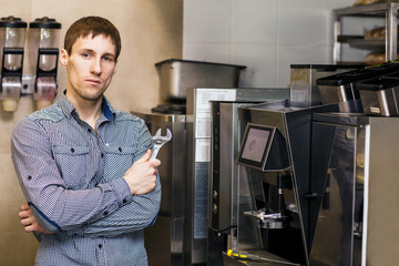 Barista standing with wrench near coffee maker