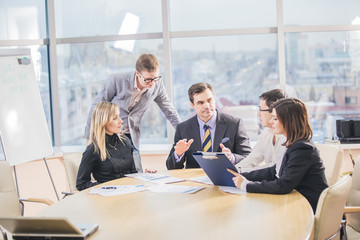 Group of successful business partners in casual communicating at meeting in office