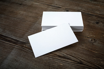 Photo of blank business cards on dark wooden background. Template for ID. Mock-up for branding identity.
