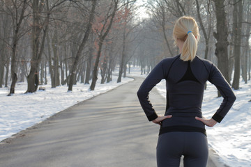 Woman winter runner resting after workout. Jogging, sport, fitness, active lifestyle concept, cold weather training