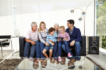 Big family with tablet PC in living room