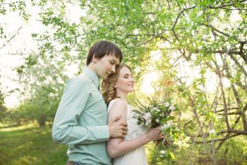 Love couple standing among blooming apple tree