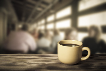 Coffee in cup on wooden table opposite a blurred background. Ton