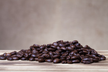 Pile of coffee beans on wooden table opposite a defocused burlap
