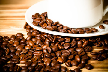 Coffee beans and coffee in white cup on wooden table for backgro