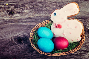 easter bunny with easter eggs   over rustic wooden background. retro style toned.