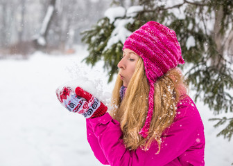 Young happy woman enjoy snow in winter city park outdoor