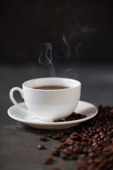 Coffee cup and saucer on a wooden table. Grey background