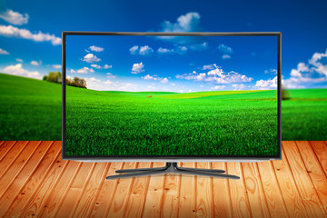 television on a wooden table on a background nature
