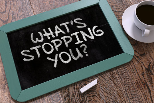 Whats Stopping You Handwritten by White Chalk on a Blackboard.