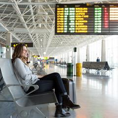 Frau am Terminal mit Handgepaeck