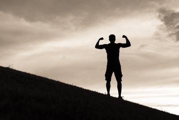 Silhouette of confident fit male flexing outdoors.