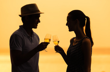 Young couple enjoying a glass of wine by the sea.