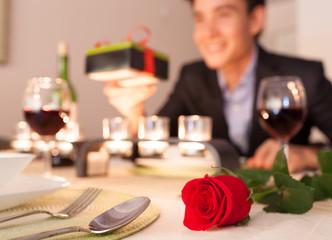 Romantic date night. (Focus on red rose)