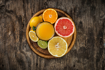 Juice glass and fresh citrus fruit