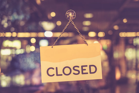 Vintage tone of :A closed sign hanging in a shop window