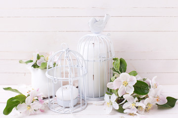 Postcard with apple blossom and candles in decorative bird cages