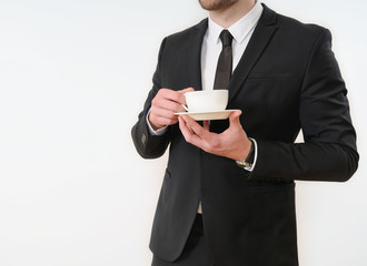 business man body side in black suit with cup of coffee on white