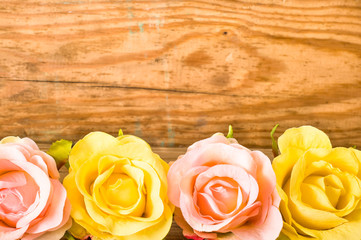 Roses flowers on wood, floral background on a vintage wooden planks useful as greeting card