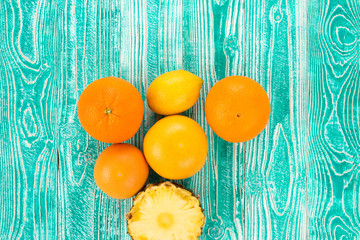 citrus fruits - lemon, grapefruit, orange, pineapple on.. turquoise colored wooden background, top view. copy space, free space for your text.