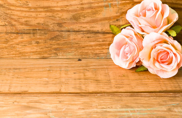 Roses on wooden boards, floral background for greeting card with copy-space