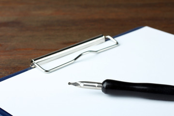 Pen lying on a sheet of a contract or on a blank sheet to fill out on the wooden table
