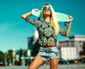 High fashion look.glamor stylish sexy beautiful young cute blond model girl in summer bright casual hipster clothes with skateboard posing behind blue sky