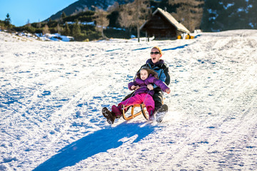 Mother and little child are sledging very fast in ski mountain r