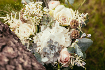 roses, succulents and other flowers in wedding bouquet on green
