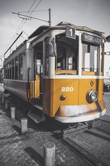 Desaturated picture of the Porto trolley except for its particular yellow.