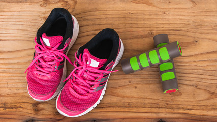Old pink sneakers with fitness dumbbells on wood background