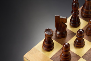 chess figures and board at black