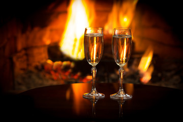 Two glasses of sparkling white wine in front of warm fireplace. Romantic, cozy relaxed magical atmosphere near fire. Valentines day concept. Background