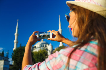 Girl  making photo by the smartphone near the Blue Mosque, Istan