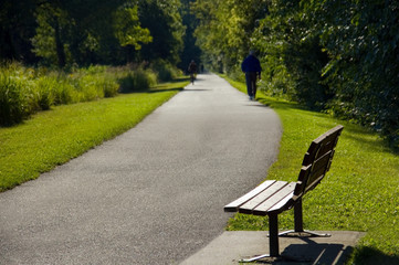 Park Bench and Person on Walking Trail Photo